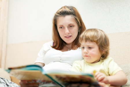 Mother and child reading  book together on couch in home photo