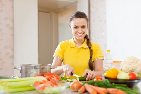 woman chopping cucumber and other vegetables at domestic kitchen photo
