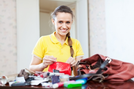Smiling girl looking for something in purse  in home Stock Photo - 18593876