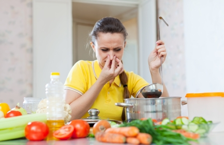 frowy:  woman holding her nose because of bad smell from soup in pan at kitchen Stock Photo