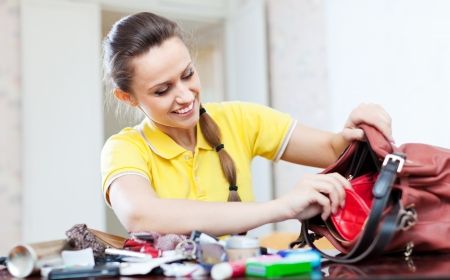 ransack: Smiling girl looking for something in handbag at table in home Stock Photo