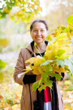 happy seasonable: Outdoor portrait of  happy mature woman with maple posy