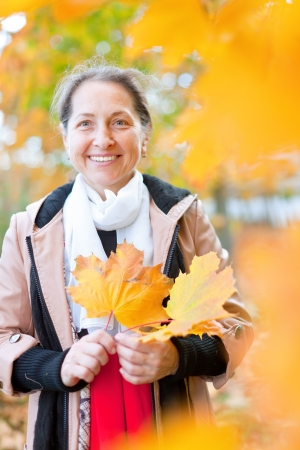 happy seasonable: Outdoor portrait of mature woman in autumn with maple leaves Stock Photo
