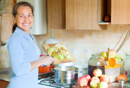 Woman brews apple jam in the kitchen photo
