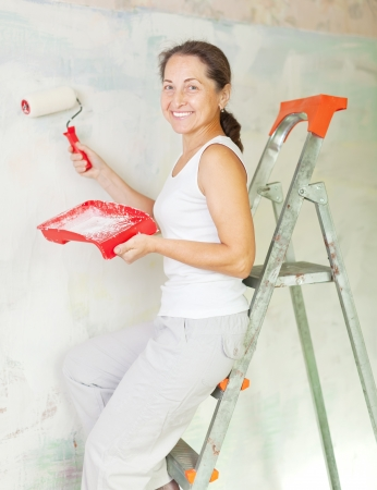 Happy woman paints wall with roller at home Stock Photo - 18654965