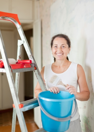 Mature woman makes repairs at home photo