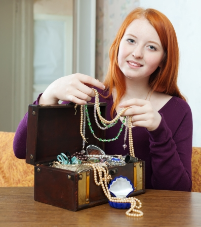 red-headed girl looks jewelry in treasure chest at home interior photo