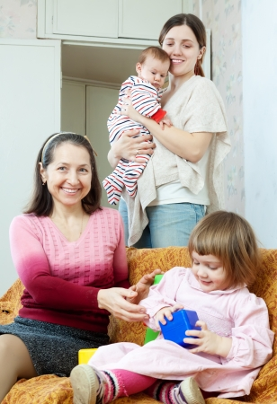 three generations of women: Happy women of three generations plays on the sofa in home