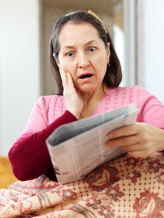 hardships: wonder mature woman having grief  after readed news in newspaper