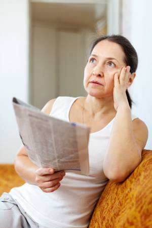 wistful:  serious and wistful  woman with newspaper at home