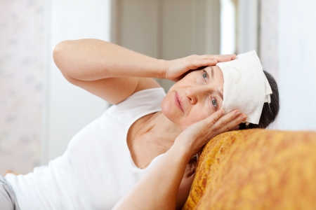 Suffering mature woman stupes  towel to her head Stock Photo