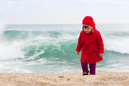 aloneness: Girl on sand beach in cold windy day Stock Photo