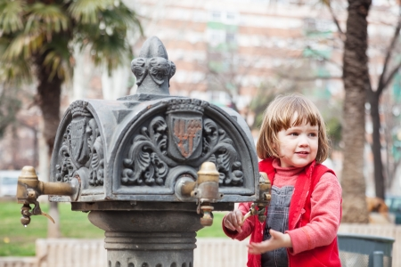 Girl using stand-pipe on street of Barcelona, Spain photo