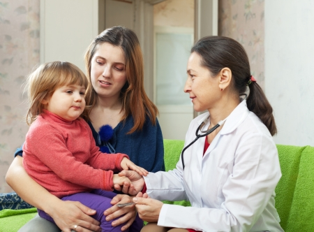 children's doctor: mature childrens doctor examining 2 years child at home