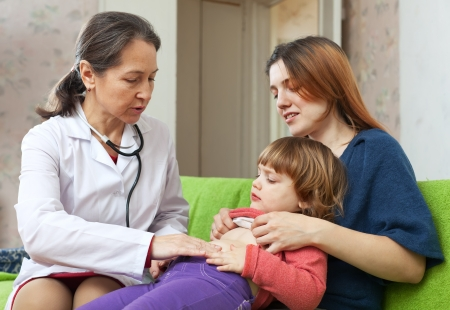 s stomach: mature  doctor examining 2 years child at home Stock Photo
