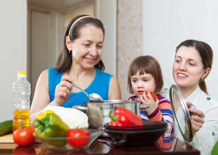 Mature woman and her adult daughter with baby girl cook veggie lunch in kitchen Stock Photo - 18786174