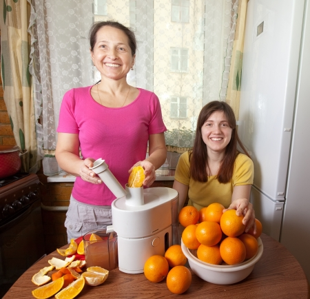 Two women  making fresh orange juice in her kitchen photo