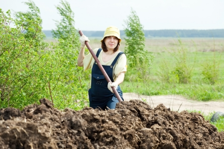 Woman works with animal manure at field photo