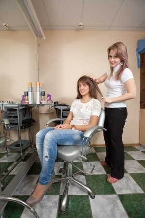 upsweep: Female hairdresser working with long-haired girl Stock Photo