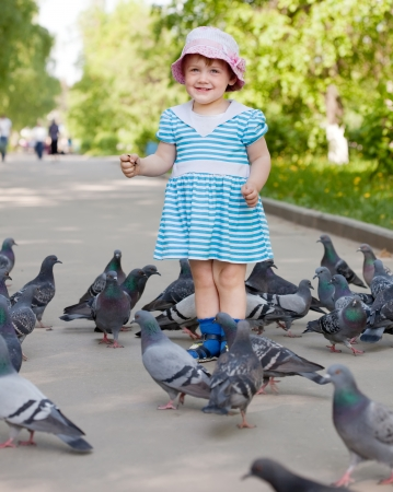 two-year girl with doves  in the city street photo