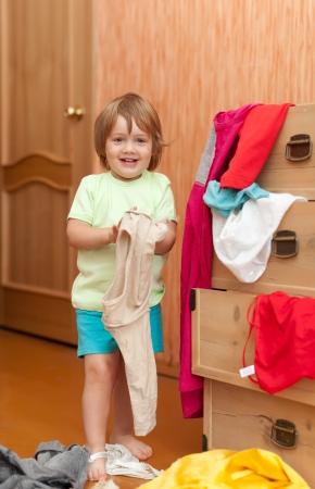 Baby girl  chooses dress at closet