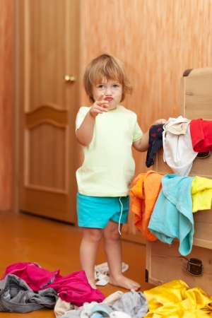 Baby girl  chooses clothes in parents closet   Stock Photo