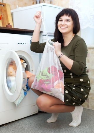 Happy housewife loading the washing machine with laundry bag photo
