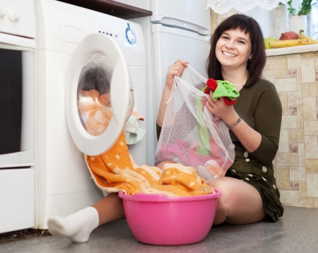 Young housewife loading the washing machine in kitchen Stock Photo - 18910942