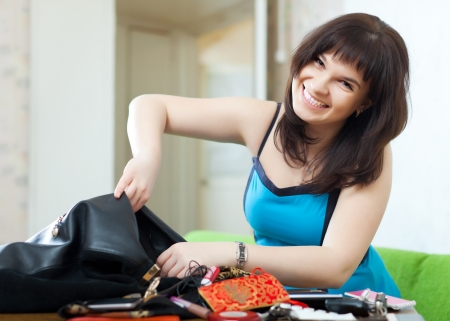positive woman can not finding anything in her purse at table  Stock Photo - 18910837