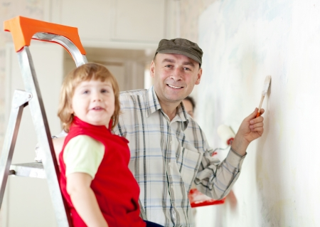 Parents with child  paints wall at home photo