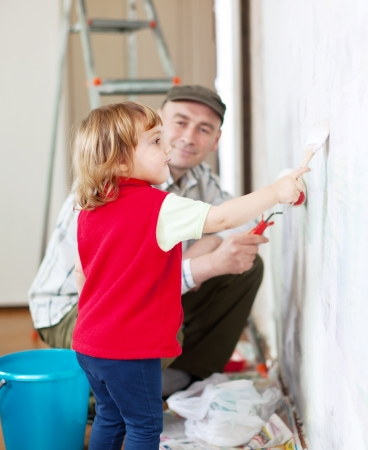 father with child paints wall  at home photo