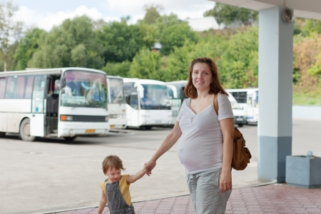 motorbus: Happy pregnant woman with child at bus station Stock Photo