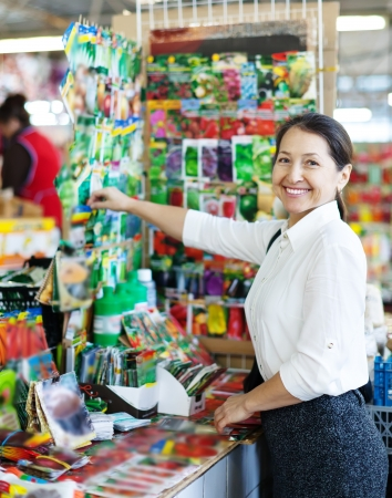 Smiling mature woman chooses packaged seeds at market for gardener photo