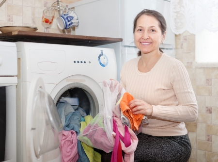 mature  woman uses bag for laundry in washing machine at her home photo