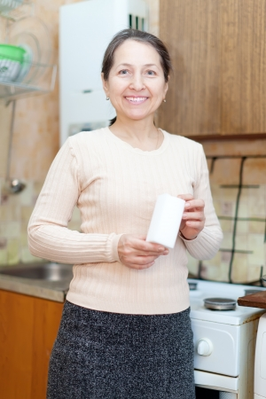 Happy mature woman with sponge in kitchen at home photo