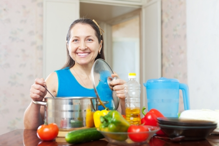 Happy mature woman with vegetables at her kitchen photo