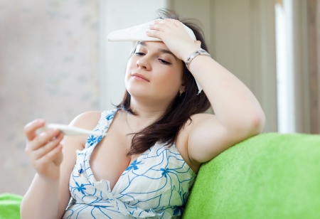 Sick woman with thermometer stupes  towel to her head photo