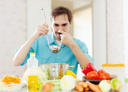 foul: Man with ladle testing foul food at kitchen Stock Photo