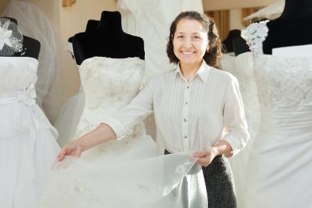 bridal salon: Mature woman shows bridal dress at wedding store Stock Photo