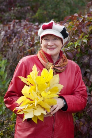 Outdoor portrait of  mature woman with maple posy photo