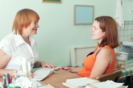 gravida: Mature doctor and pregnant woman in clinic