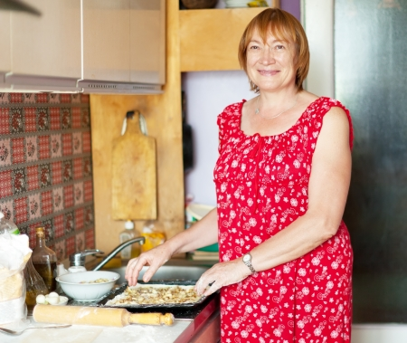 pasty: Mature woman makes pasty with fillings in her kitchen Stock Photo