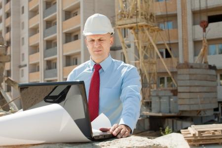 building site: Portrait of builder works at construction site