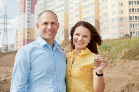 Happy couple with key against new brick house    photo