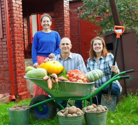 Man and two women with  harvested vegetables in garden photo