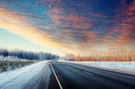 Winter road through snowy fields and forests photo