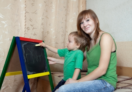 mothering: Mother and child draws on the blackboard with chalk