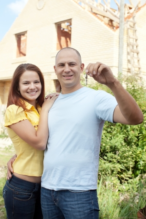 poling: Happy couple with key against building new brick house