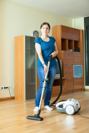 full length shot of girl cleans with vacuum cleaner at home photo