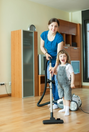Woman teaches baby girl to use the vacuum cleaner at home photo
